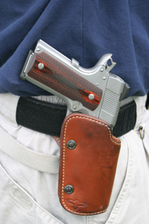 A Colt 1911 pistol riding in a good quality level-one belt handgun holster for personal defense